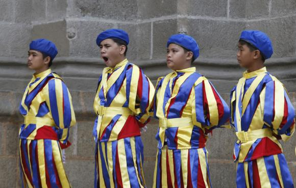 A boy yawns as schoolchildren dressed as Vatican Swiss guards rehearse outside the Manila Cathedral for the upcoming papal visit in Manila